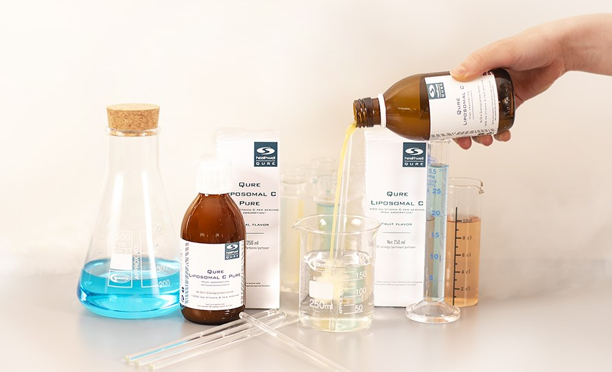 Product packaging, bottles and measuring glasses on a table. A hand pours a bottle of QURE Liposomal C into a measuring glass with water.