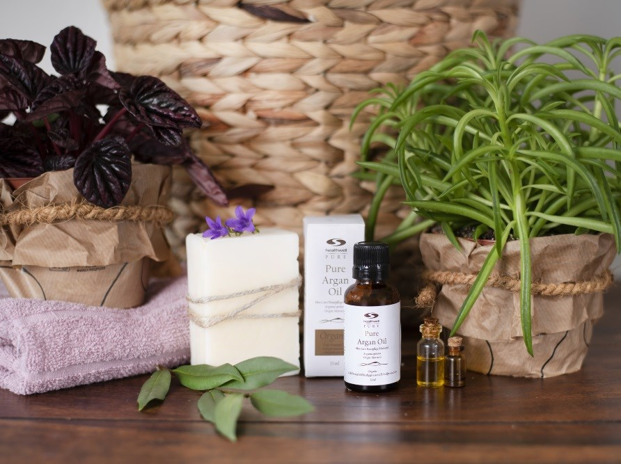 pure argan oil sitting with the carton, plants and a soap in front of a basket.